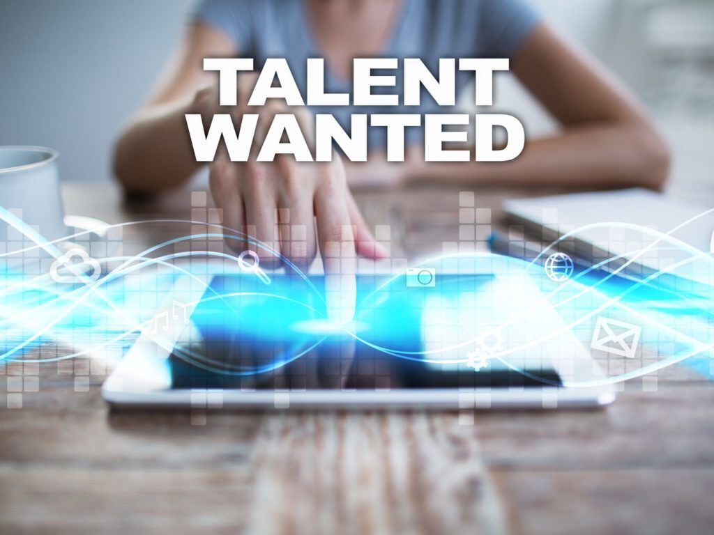 Woman using tablet pc, pressing on virtual screen and selecting talent wanted.